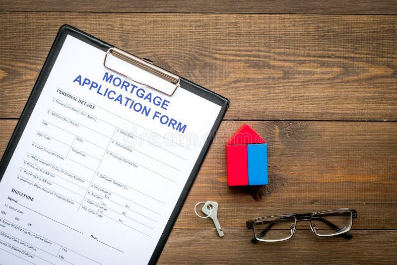 Concepto de la hipoteca La forma de la solicitud de hipoteca cerca de la llave y de la casa hizo de constructor en la opinión de  fotografía de archivo