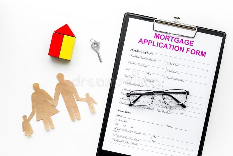 Concepto de la hipoteca La forma de la solicitud de hipoteca cerca de la llave y de la casa hizo del constructor, recorte de la f foto de archivo libre de regalías
