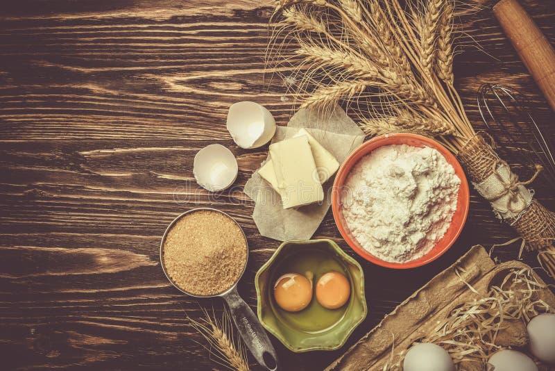 Concepto de la hornada - los ingredientes de la hornada untan con mantequilla, flour, azucaran, los huevos en fondo de madera rús fotos de archivo