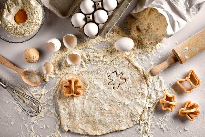 Concepto de la hornada: pasta cruda para la galleta, los huevos, la harina, los cortadores en la forma de la estrella y la maripo imagenes de archivo