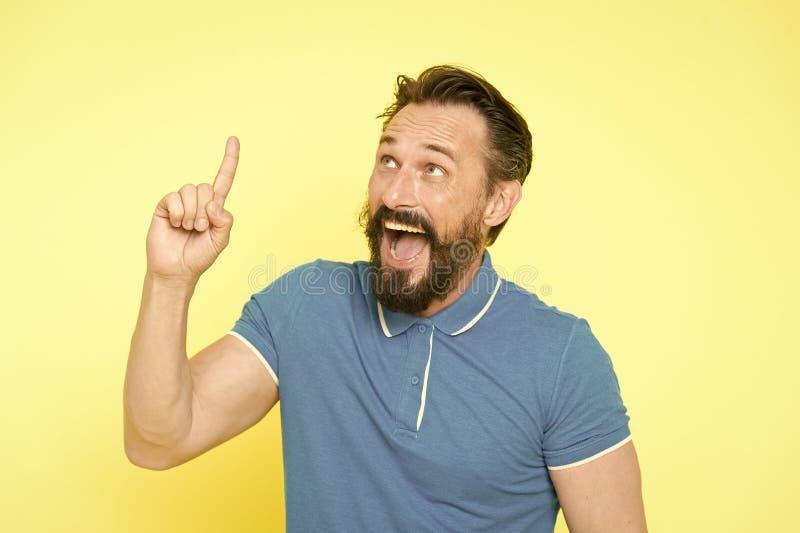 Concepto de la idea fresca Hombre maduro sonriente hermoso que mantiene el finger aumentado y que mira hacia arriba mientras que  imagen de archivo