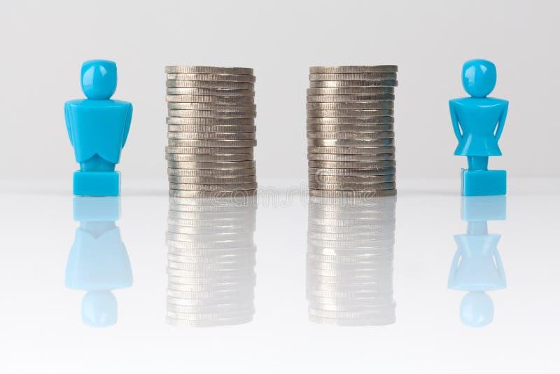 Concepto de la igualdad de salario mostrado con las estatuillas y las monedas imagen de archivo
