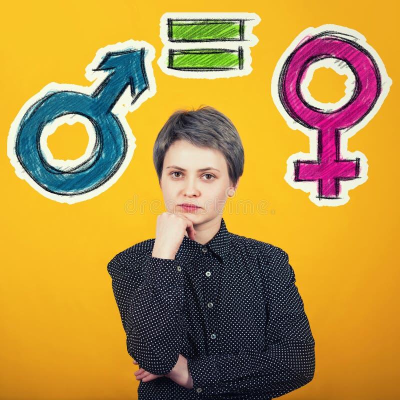 Concepto de la igualdad de género con el símbolo masculino y femenino sobre la pared amarilla Met?fora social del problema de la  foto de archivo