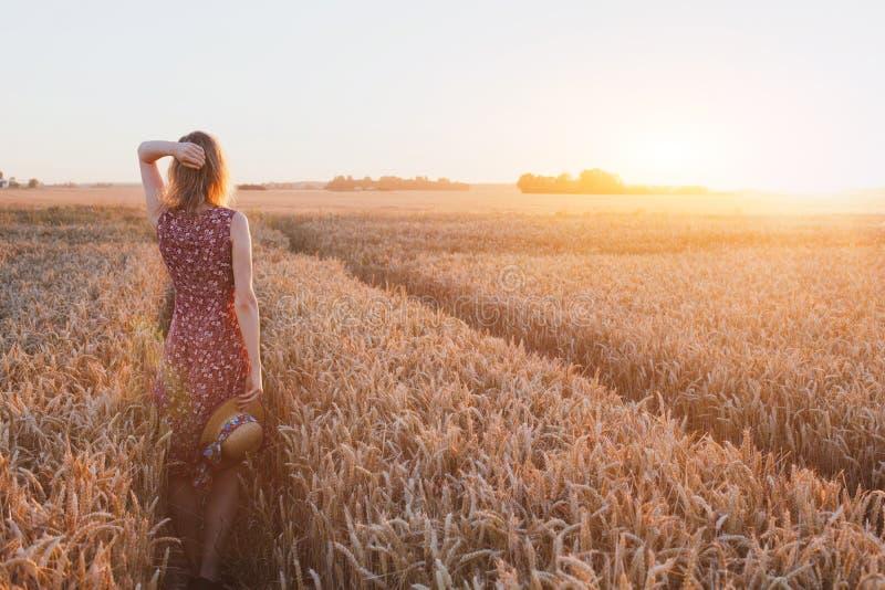 Concepto de la inspiración o el esperar, mujer joven hermosa feliz en campo de la puesta del sol imagen de archivo libre de regalías