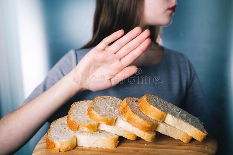 Concepto de la intolerancia del gluten La chica joven rechaza comer el brea blanco fotografía de archivo