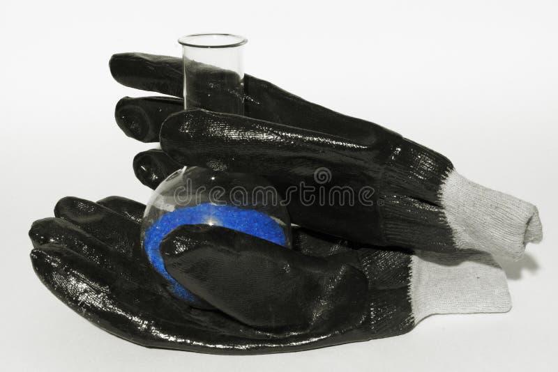 Concepto de la investigación del laboratorio - frasco del cristal azul en los guantes imagenes de archivo