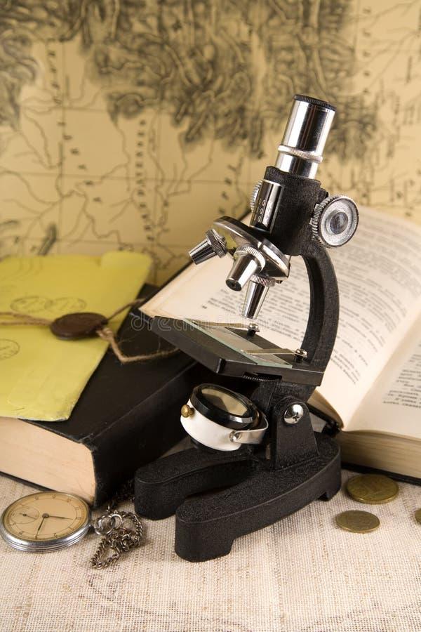 Concepto de la investigación - microscopio y libros foto de archivo