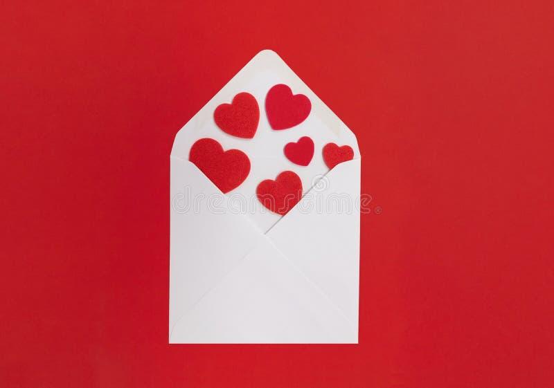 Concepto de la letra de amor Sobre blanco con los corazones que se derraman hacia fuera, con un fondo rojo fotografía de archivo
