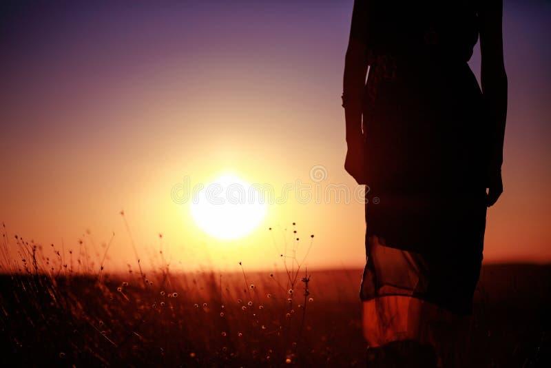 Concepto de la libertad Mujer hermosa que disfruta de la puesta del sol en el campo fotos de archivo libres de regalías