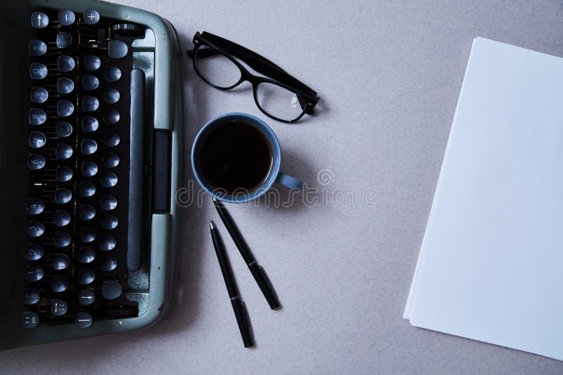 Concepto de la literatura, del autor y del escritor, de la escritura y del periodismo: máquina de escribir, taza de café y vidrio fotografía de archivo