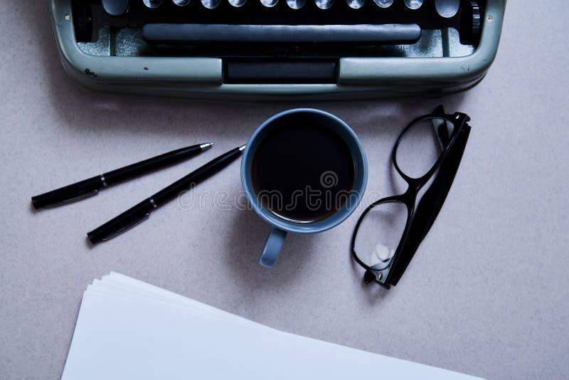Concepto de la literatura, del autor y del escritor, de la escritura y del periodismo: máquina de escribir, taza de café y vidrio imagen de archivo libre de regalías