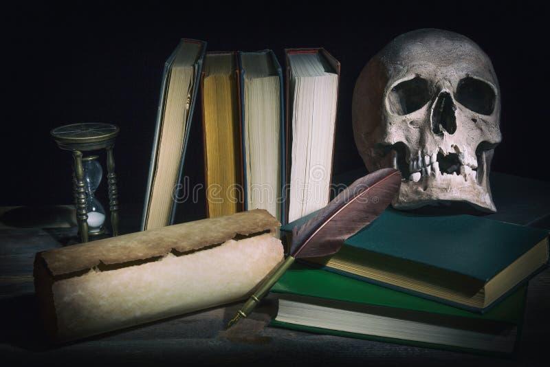 Concepto de la literatura Libros viejos con el cráneo cerca de la voluta, de la pluma de la pluma de canilla y del reloj de arena fotografía de archivo libre de regalías