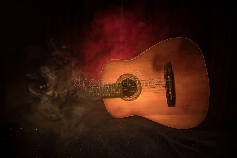 Concepto de la música Guitarra acústica en un fondo oscuro bajo haz de luz con humo Guitarra con las secuencias, cierre para arri fotografía de archivo libre de regalías