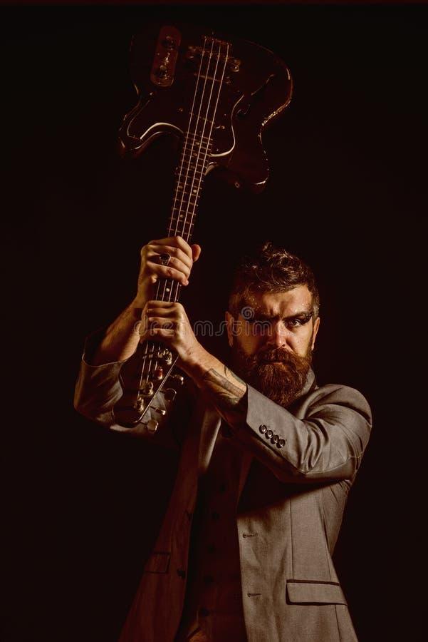 Concepto de la música Guitarra barbuda del control del hombre en manos en el festival de música Hombre con el instrumento musical foto de archivo libre de regalías