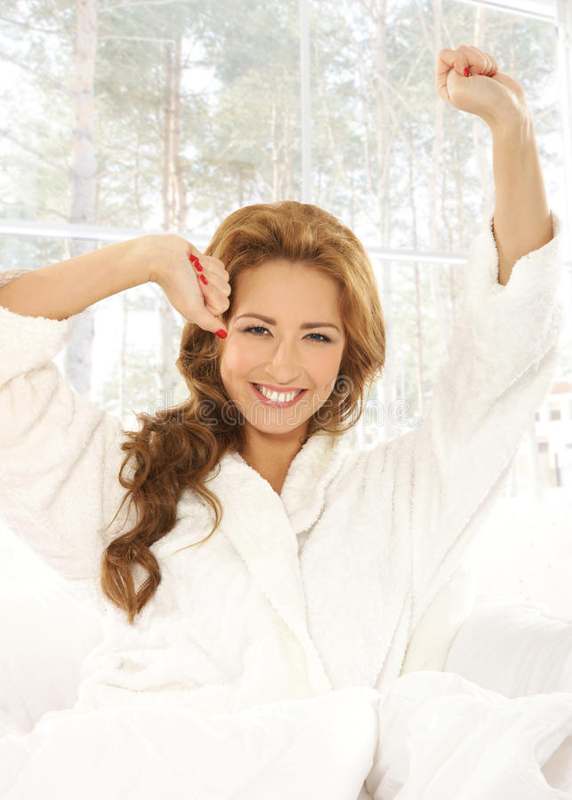 Concepto de la mañana: mujer atractiva joven en la cama fotos de archivo