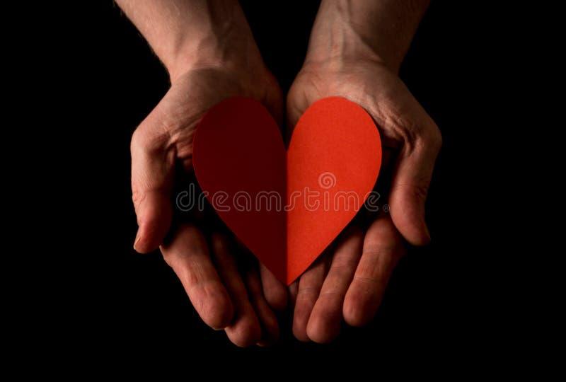 Concepto de la mano amiga, palmas de las manos del hombre encima de llevar a cabo un corazón rojo, dando el amor, alcanzando haci imagen de archivo libre de regalías
