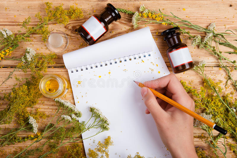 Concepto de la medicina alternativa - la mano escribe una receta en libreta encendido fotografía de archivo libre de regalías