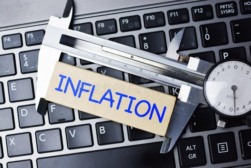 Concepto de la medida de la inflación con la herramienta del calibrador en el teclado de ordenador fotos de archivo