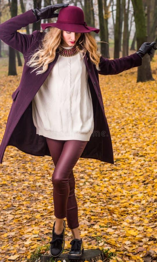 Concepto de la moda de la caída, mujer elegante hermosa en parque imagenes de archivo