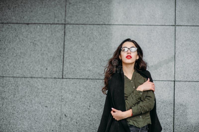 Concepto de la moda: chica joven hermosa con el pelo largo, los vidrios, los labios rojos que se colocan cerca de la pared modern fotografía de archivo