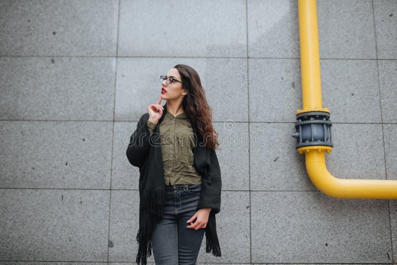 Concepto de la moda: chica joven hermosa con el pelo largo, los vidrios, los labios rojos que se colocan cerca de la pared modern foto de archivo libre de regalías