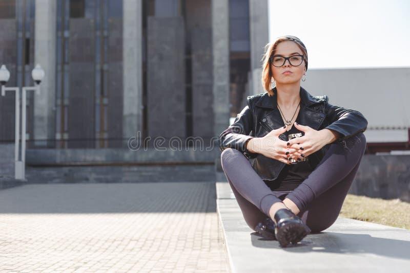 Concepto de la moda de la calle - muchacha fresca elegante en el estilo del negro de la roca que se sienta entre el fondo urbano  fotos de archivo libres de regalías