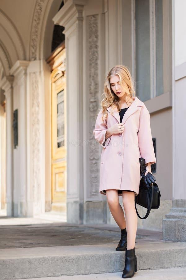 Concepto de la moda de la calle: retrato de la mujer hermosa joven que lleva la capa rosada con el bolso que camina en la ciudad  fotografía de archivo libre de regalías