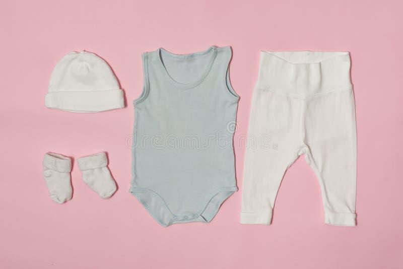 Concepto de la moda del bebé en un fondo rosado Casquillo, mono, pantalones y calcetines fotografía de archivo