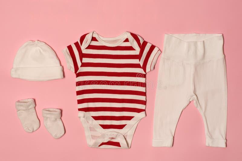 Concepto de la moda del bebé en un fondo rosado Casquillo, mono, pantalones y calcetines fotos de archivo
