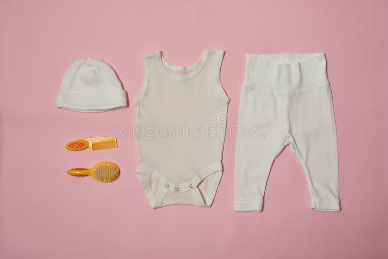 Concepto de la moda del bebé en un fondo rosado Ropa y accesorios para el cuidado foto de archivo libre de regalías