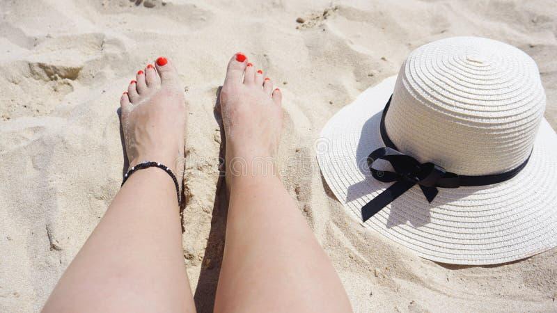 Concepto de la moda de las vacaciones de verano - piernas de la mujer y sombrero del sol que broncean en la playa imágenes de archivo libres de regalías