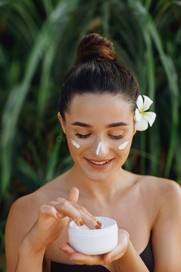 Concepto de la mujer de la belleza Cuidado de piel Retrato del modelo femenino que sostiene y que aplica la crema hidratante cosm imágenes de archivo libres de regalías