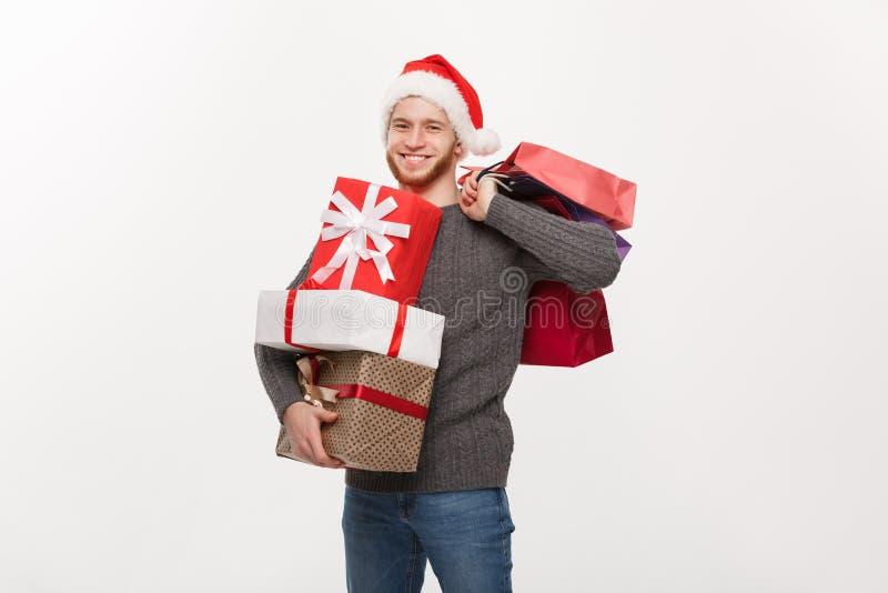 Concepto de la Navidad - hombre hermoso joven con la barba que sostiene muchos presentes y panieres con el facial feliz imagen de archivo libre de regalías