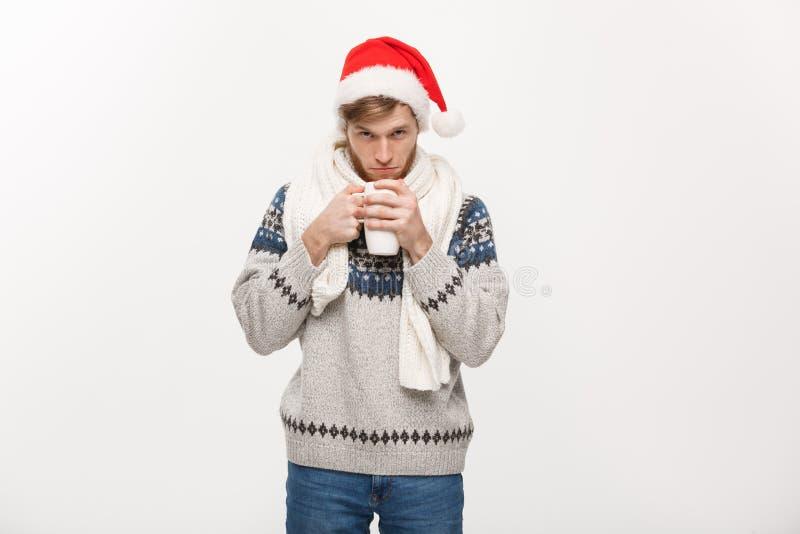 Concepto de la Navidad - hombre joven de la barba en el suéter y el sombrero de santa que sostienen una taza de café caliente ais fotografía de archivo libre de regalías