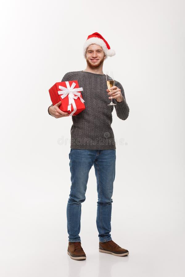 Concepto de la Navidad - hombre joven feliz con la barba que lleva a cabo el presente y champán que celebran para la Navidad aisl fotografía de archivo