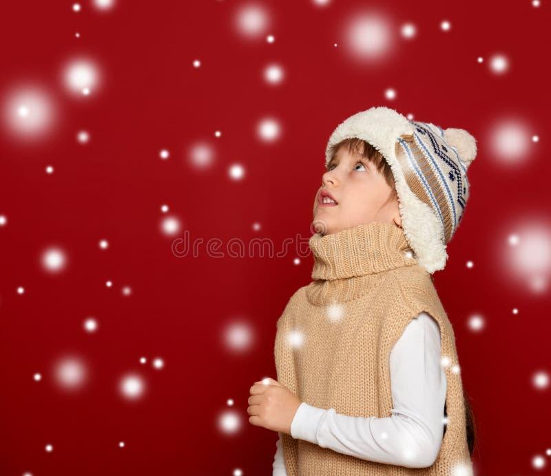 Concepto de la Navidad - muchacha en sombrero y suéter en lo rojo del fondo fotos de archivo