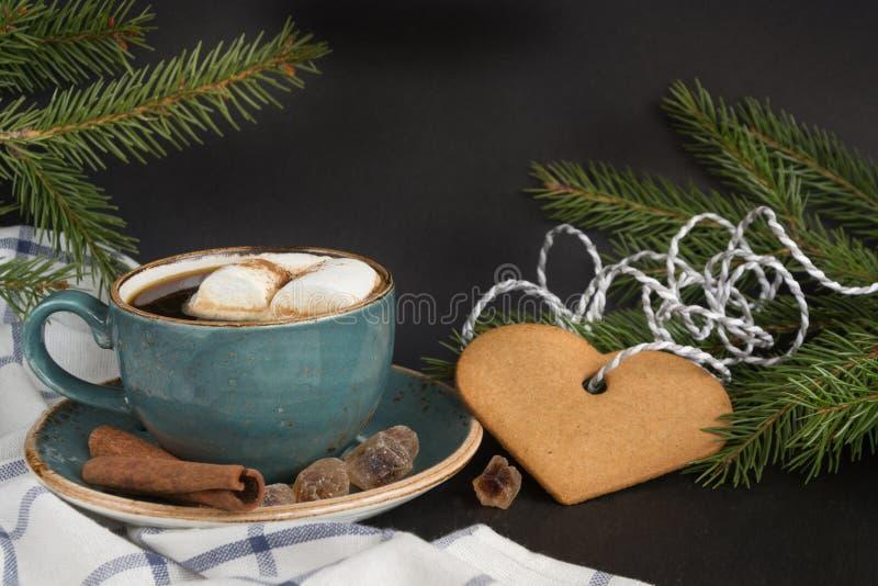Concepto de la Navidad Taza azul de café caliente con la melcocha y las galletas en un fondo negro con las ramas de árbol de navi foto de archivo