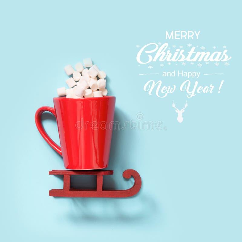 Concepto de la Navidad Taza roja con la melcocha en sleidge rojo sobre fondo azul cuadrado Alegrías del día de fiesta imagen de archivo libre de regalías