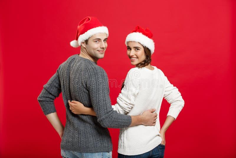 Concepto de la Navidad - vista trasera de los pares jovenes preciosos del retrato que abrazan sobre fondo rojo foto de archivo