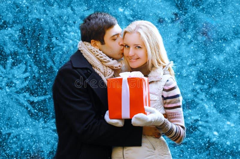 Concepto de la Navidad y de la gente - hombre feliz que da un regalo de la caja imagen de archivo