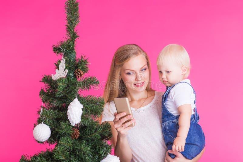 Concepto de la Navidad y del día de fiesta - retrato de la mujer sonriente con su pequeña hija que adorna el árbol de navidad foto de archivo libre de regalías