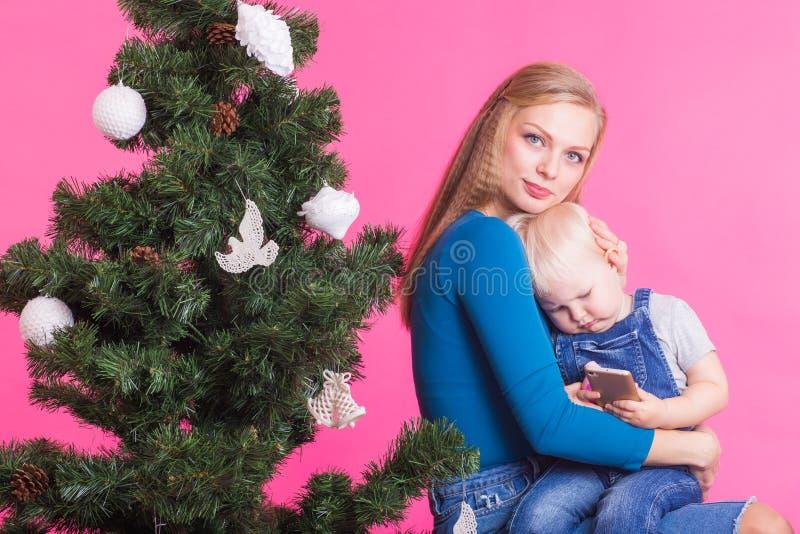 Concepto de la Navidad y del día de fiesta - retrato de la mujer sonriente que detiene a su pequeña hija cerca del árbol de navid fotos de archivo