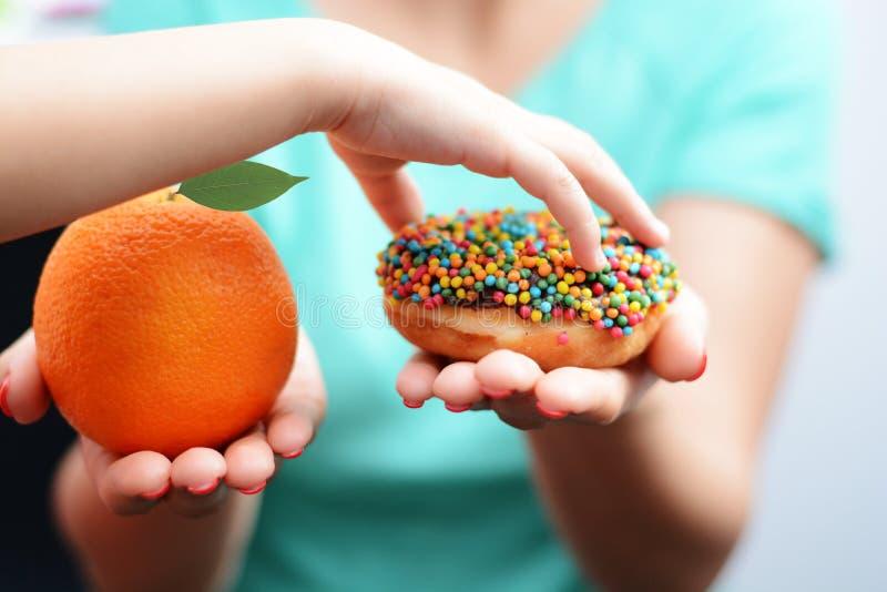 Concepto de la obesidad del niño con la mano de la niña que elige un buñuelo dulce y malsano en vez de una fruta foto de archivo libre de regalías