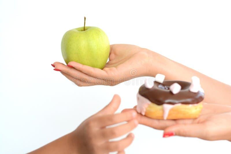 Concepto de la obesidad del niño con la mano de la niña que elige un buñuelo dulce y malsano en vez de una fruta imagen de archivo