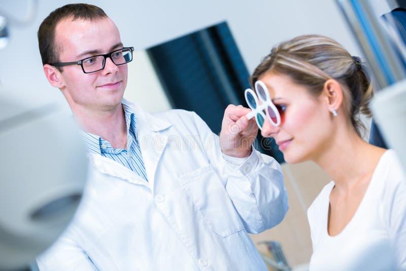 Concepto de la optometría - mujer bastante joven que la tiene ojos examinados imagenes de archivo