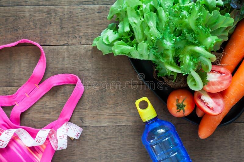 Concepto de la p?rdida de la aptitud y de peso Sujetador del deporte de la mujer y comidas sanas fotos de archivo