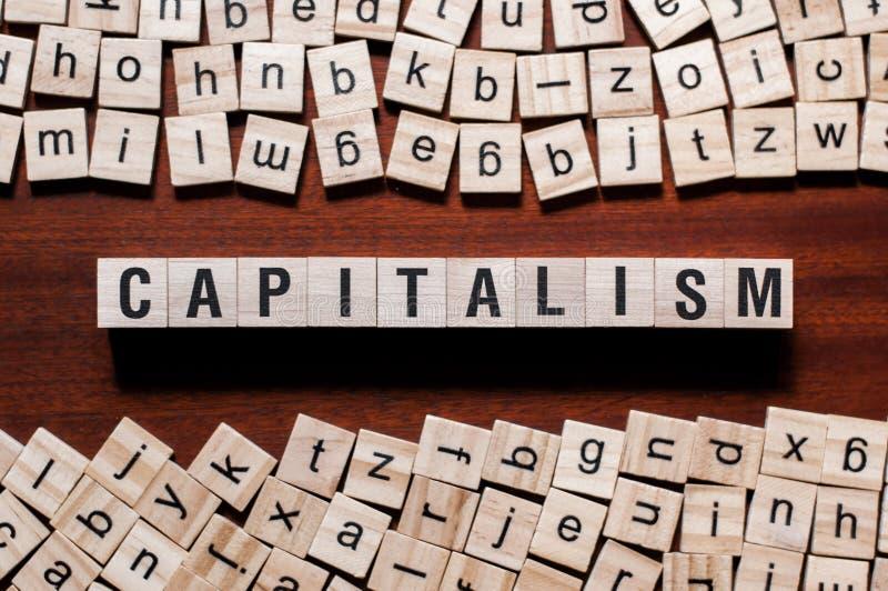 Concepto de la palabra del capitalismo en los cubos fotografía de archivo