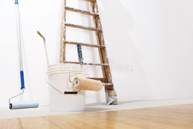 Concepto de la pared del pintor, escalera, cubo, pintura del rollo en el piso fotos de archivo libres de regalías