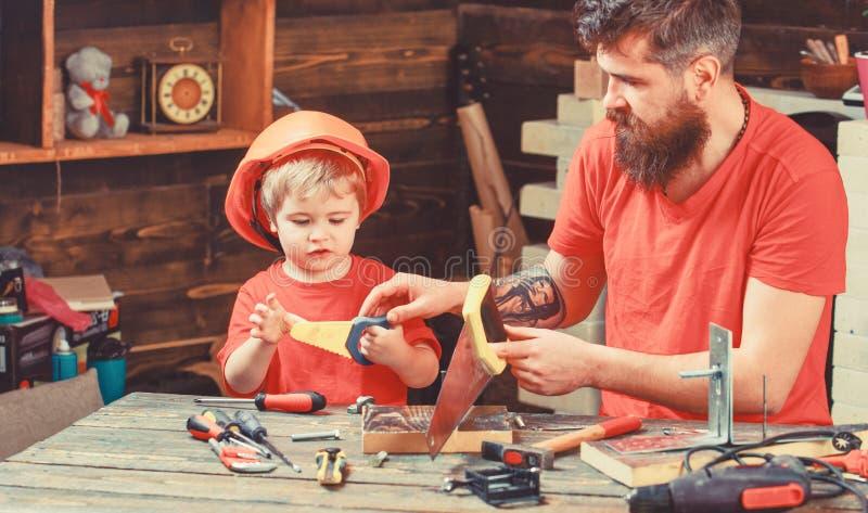 Concepto de la paternidad Muchacho, niño ocupado en casco protector aprendiendo utilizar el handsaw con el papá Padre, padre con  fotos de archivo libres de regalías