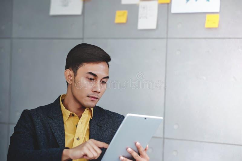 Concepto de la pequeña empresa y de la estrategia Hombre de negocios joven en sala de reunión de la oficina Trabajo con la tablet imagenes de archivo